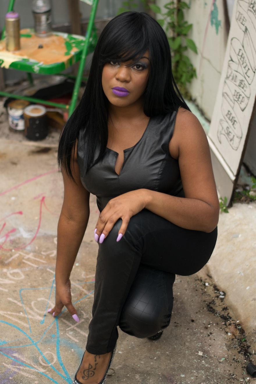 Belon kneels with legs crossed with sidewalk chalk below her on the ground and graffiti and spray paint cans placed artistically behind her.
