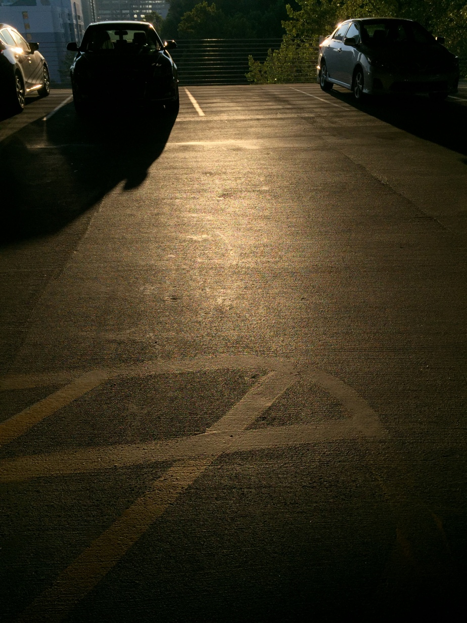 Early morning sunlight glows on the ground of a parking deck.