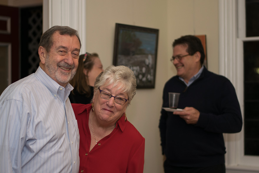 Mary Ann and her husband smile for the camera in the room where her artwork is displayed.