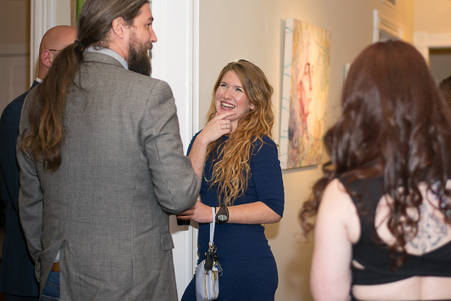 Katherine laughs as she discusses the gallery opening with visitors.