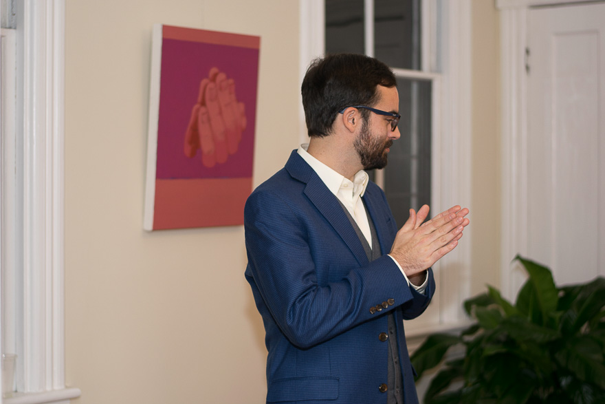 Artist Nathan Mullins inadvertently embodies his painting, , by rubbing his hands together during the gallery opening of Anomalous Art Gallery.