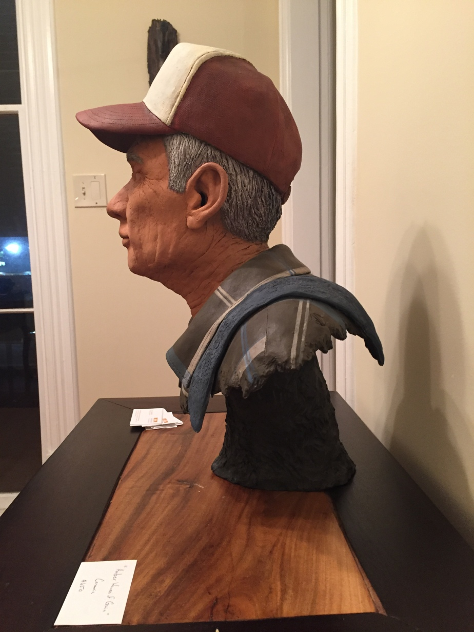 A clay bust of a man's shoulder and head.