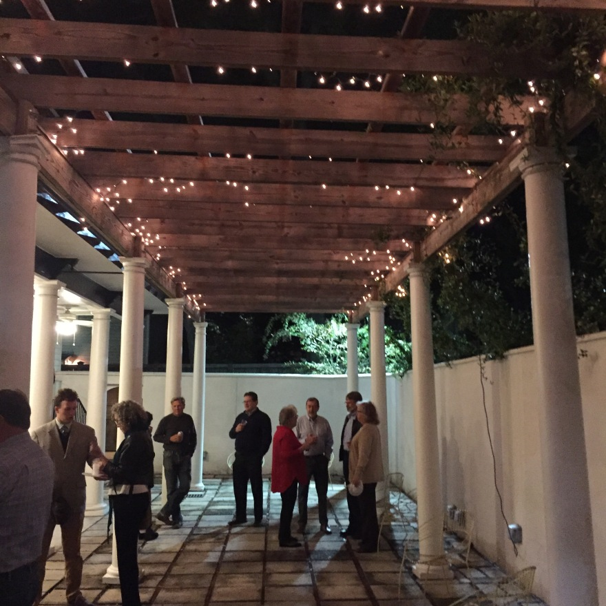 Artists and gallery attendees talk under a pergola adorned with hanging vines and tea lights.