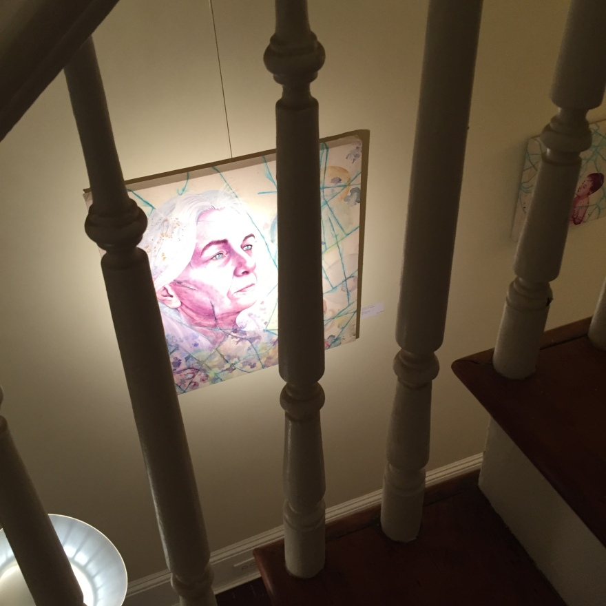 A photo of Katherine's painting through the spools of the bannister on the stairs of the home.