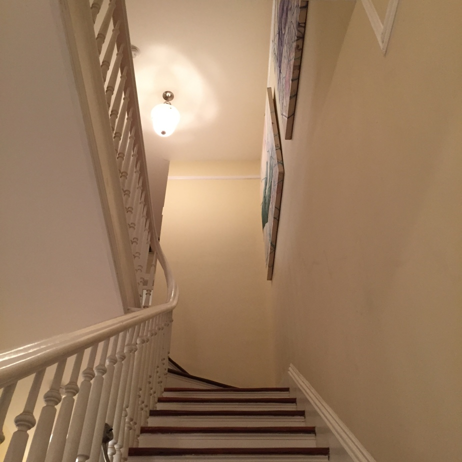 Staircase in a historic home with the original bannister leading up to the 2nd floor. Glimpses of portraits can be seen towards the top of the wall.