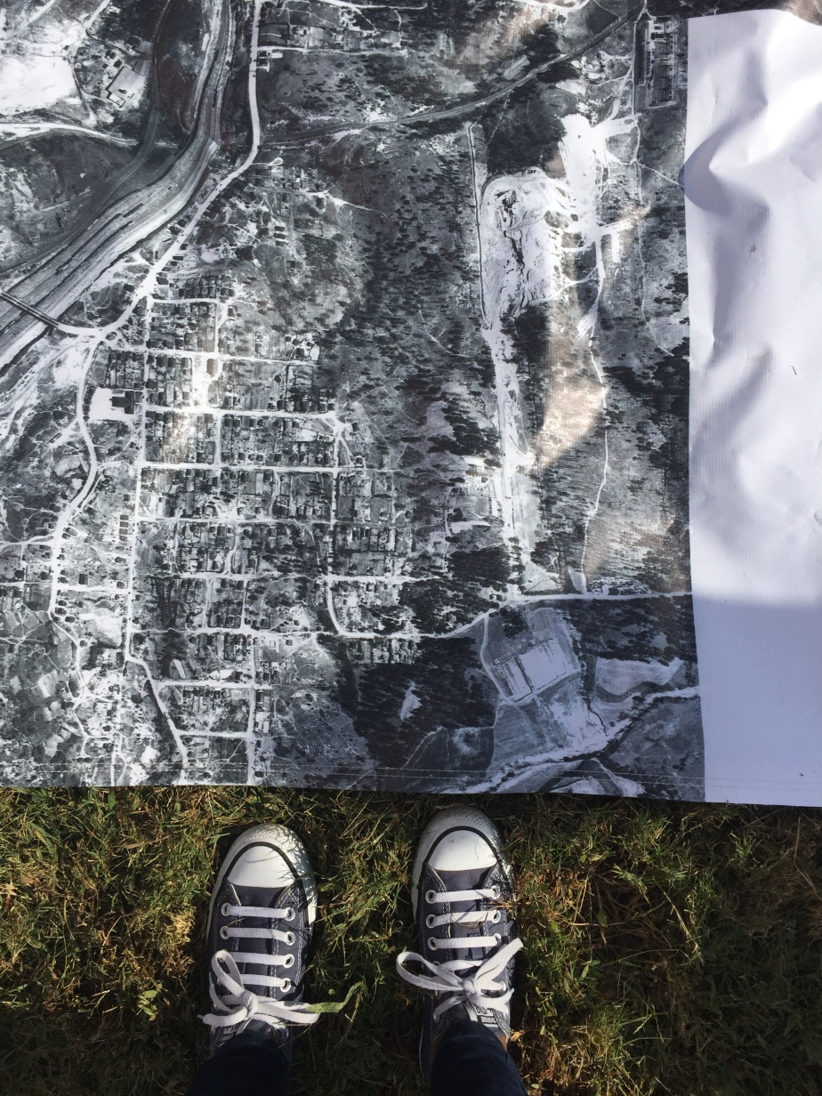 Mobile photo of a black and white aerial map and two shoes.