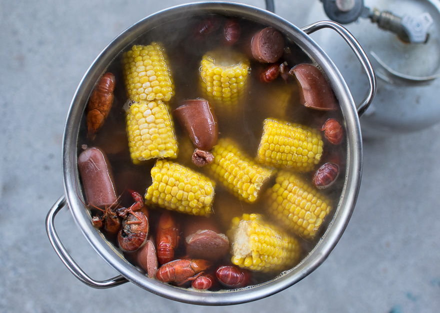 Cooked corn, sausage, potatoes, crawfish float at the top of the pot.