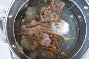 A seafood boil packet in a pot of water with three clusters of crab legs.