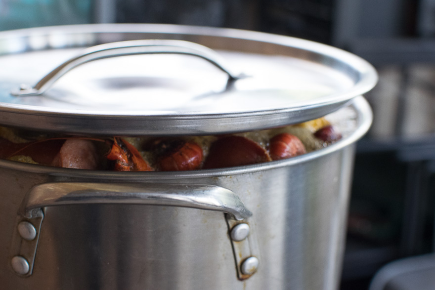 The top of the pot lifts slightly from the rim of the pot as the seafood boil rises to the top of the pot.