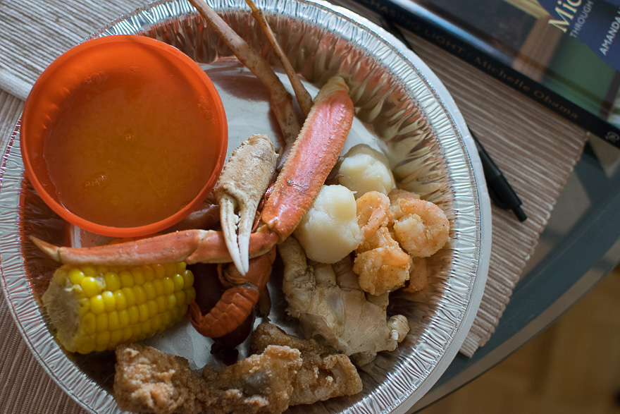 Small aluminum pan with corn, fried fish, fried shrimp, potatoes, crab legs, and a small dish of garlic butter.