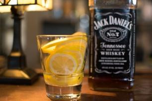 Lemon slices look appetizing in front of a Jack Daniel's bottle.