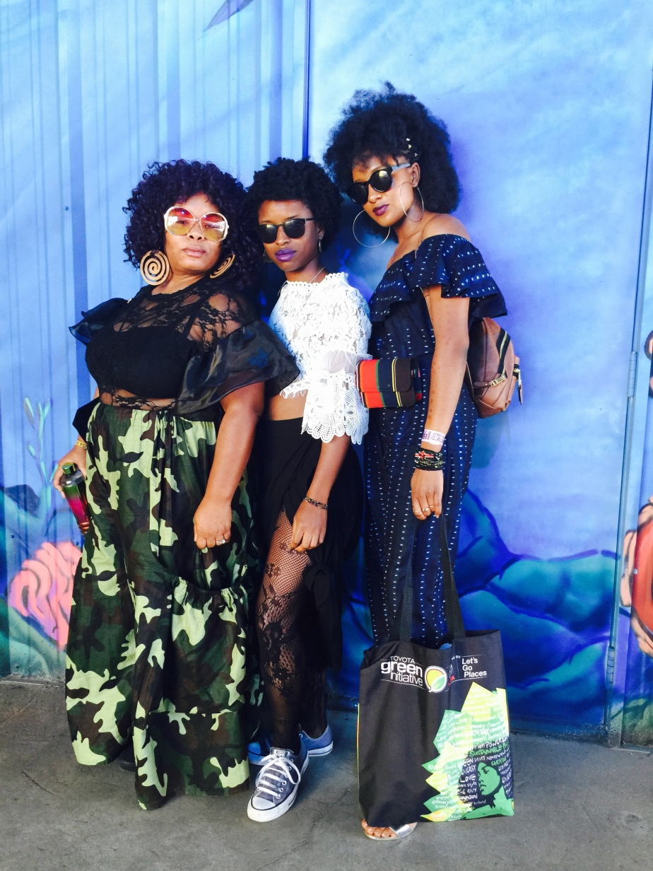Three black women pose for a photo in front of a blue wall at Afropunk.