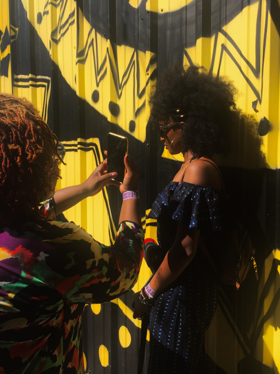 A woman takes a profile photo of another woman against a black and yellow painted corrugated wall.