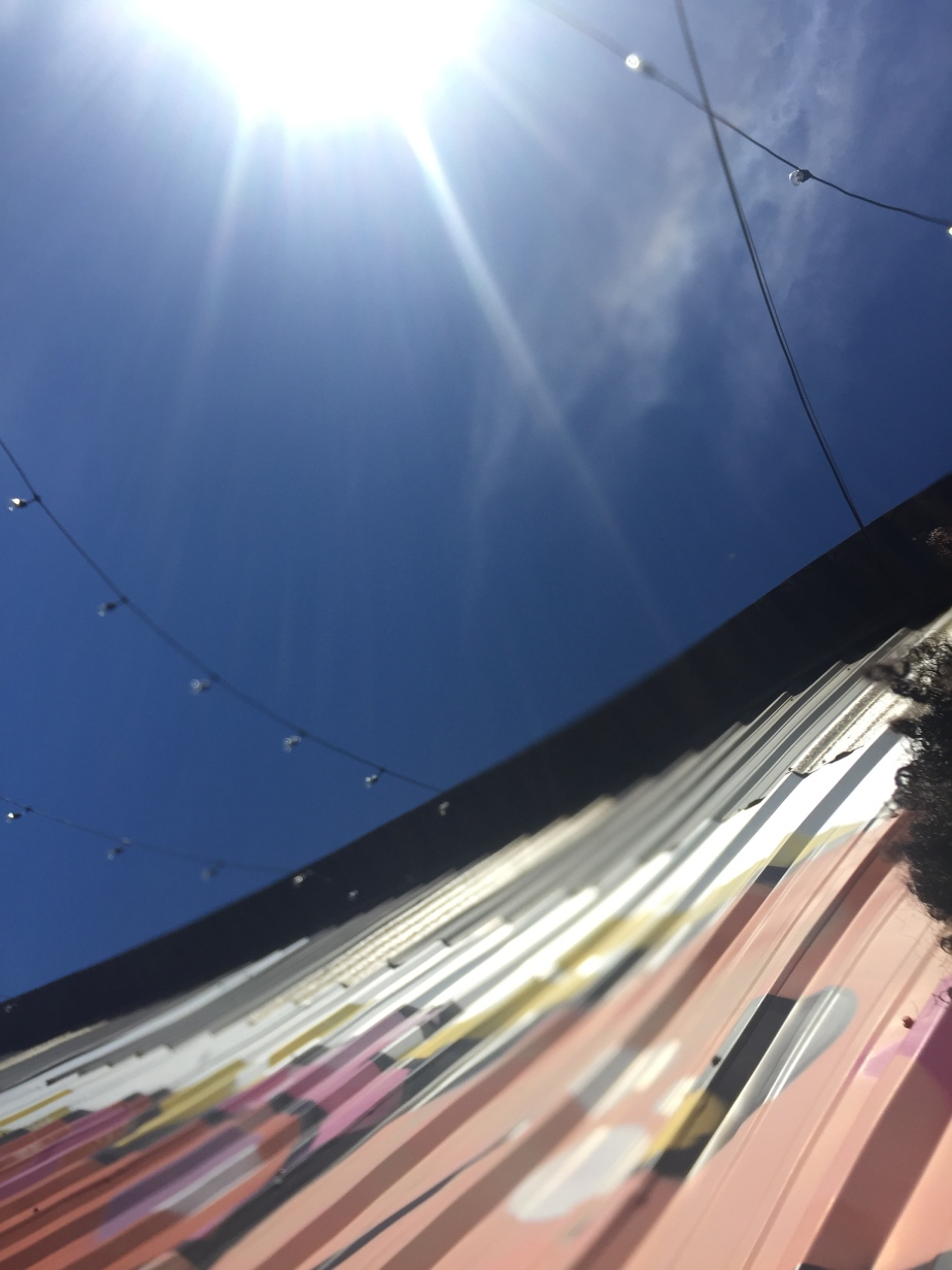 An accidental photo of a painted corrugated wall, the sky, and part of my hair.
