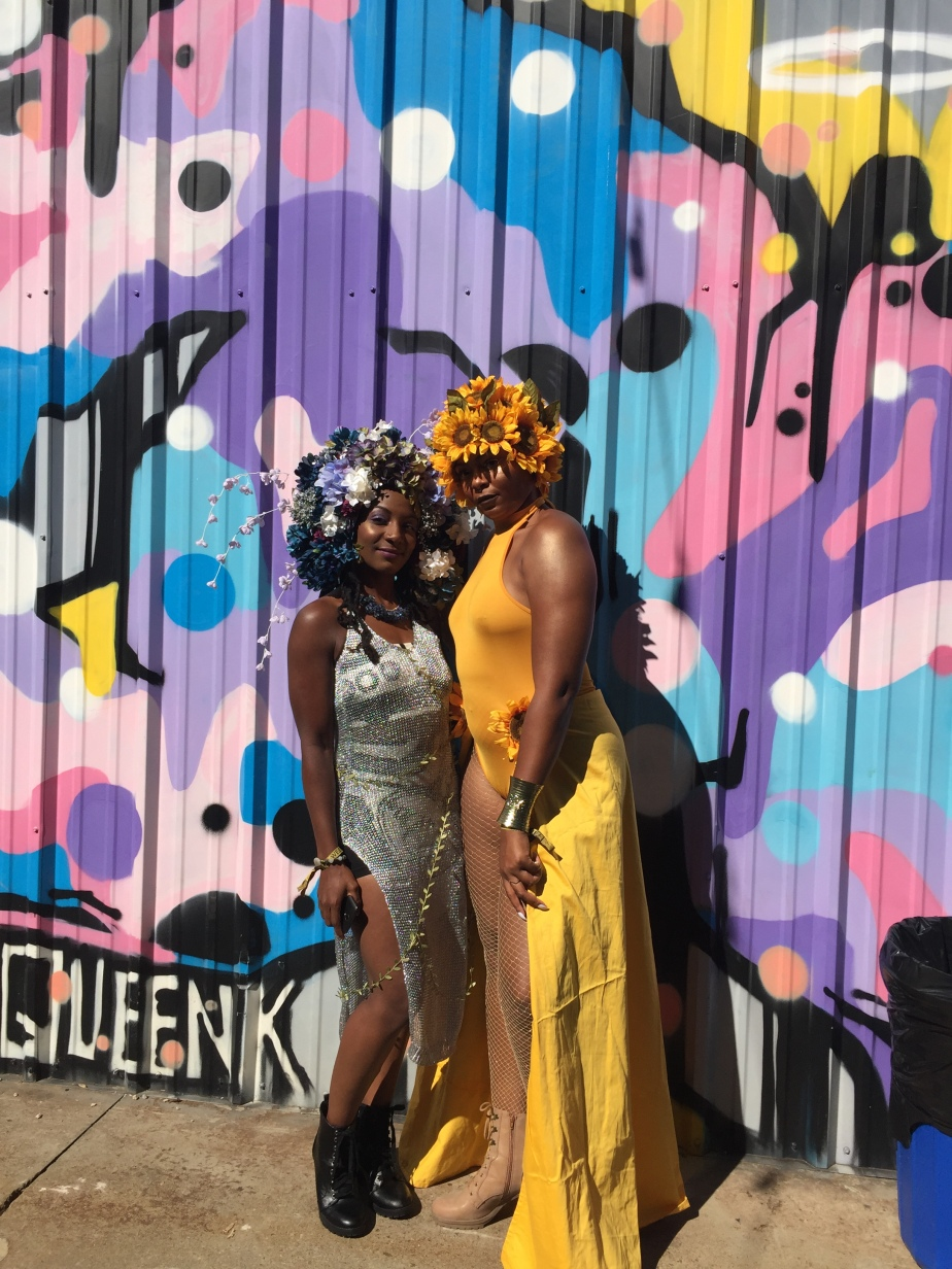 Two women pose for a photo against a colorfully painted corrugated wall. Both women wear flowers on their heads.