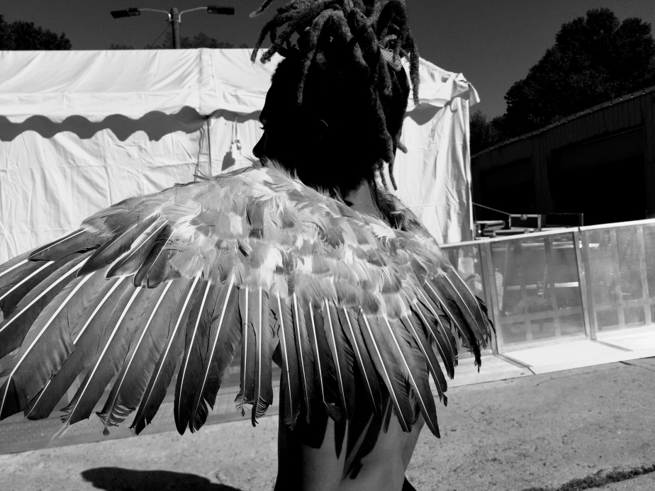 A stark black and white photo of a man with wings on his back.