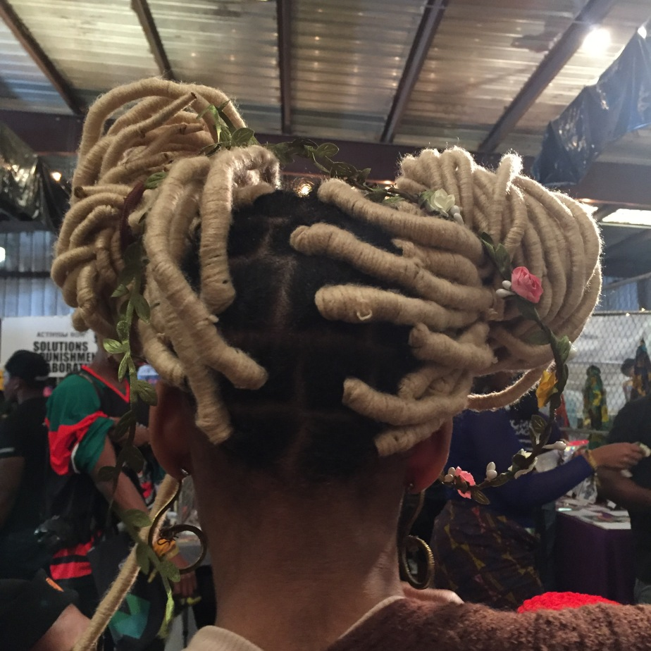 A photo of the back of a woman's head. Her hair is styled in two side buns of yarned locs with flowers adorning her hair.