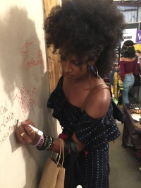 Aisha signs a cloth wall.