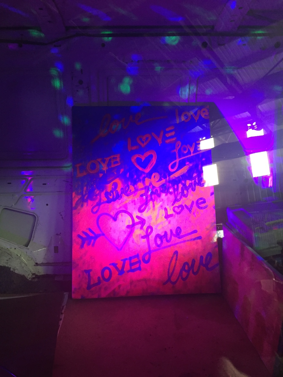 "A poster bathed in neon pink and blue light with the words ""love"" written on it."