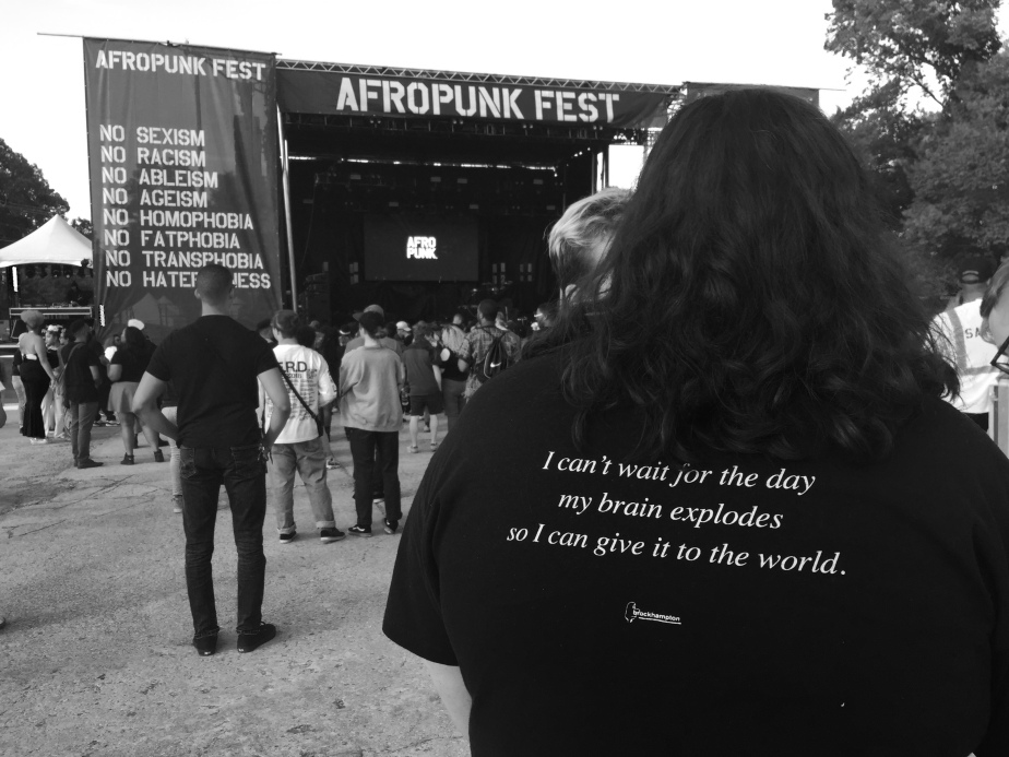 "The back of a man's shirt reads: ""I can't wait for the day my brain explodes so I can give it to the world."""