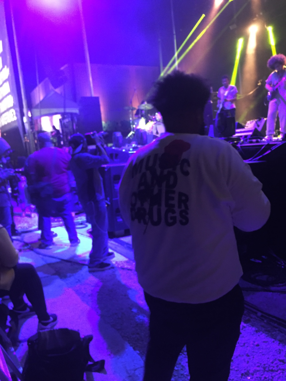 "A back of a man's shirt reads: ""Music and other drugs."""